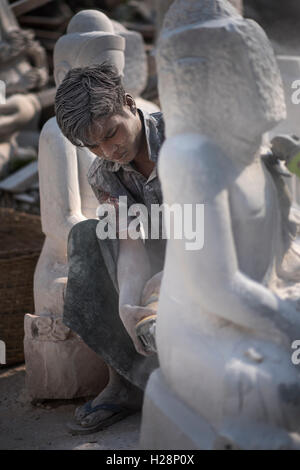 A local man carving a marble Buddha statue using an angle grinder, Amarapura, near Mandalay, Myanmar. - Stock Photo