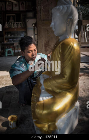 A local young man paints a Buddha statue in his workshop, Amarapura, Myanmar. - Stock Photo