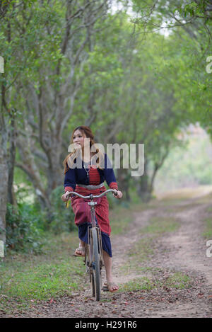 Young Asian women riding an old bike in field.Thailand - Stock Photo