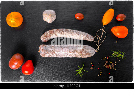 tasty delicious smoked dried sausages, thin salami and red, yellow tomatoes, garlic, peppers, rosemary on slate - Stock Photo