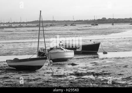 Black and white image of three boats stranded in mud at low tide at Nore Rithe Emsworth Hampshire Uk - Stock Photo