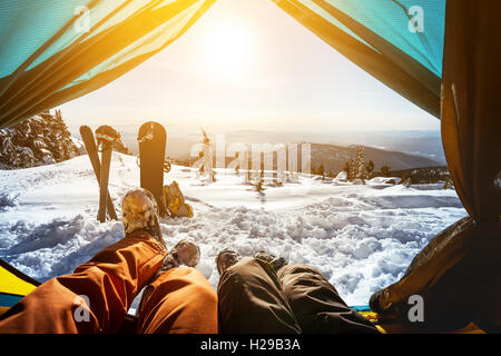 Snowboarders posing on blue sky backdrop in mountains - Stock Photo