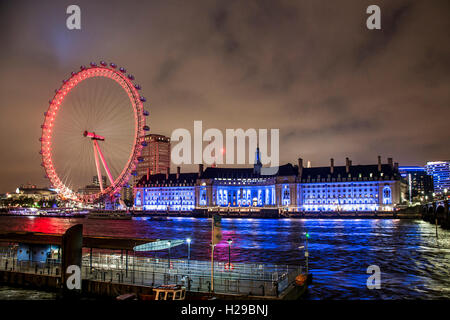 The London Eye ferris wheel illuminated city night shot - Stock Photo