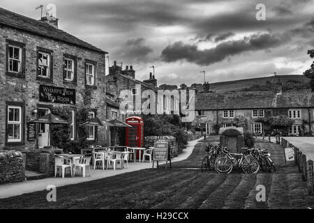 Black and white landscapes: Burnsall village with a traditional red telephone box, North Yorkshire, England, UK - Stock Photo