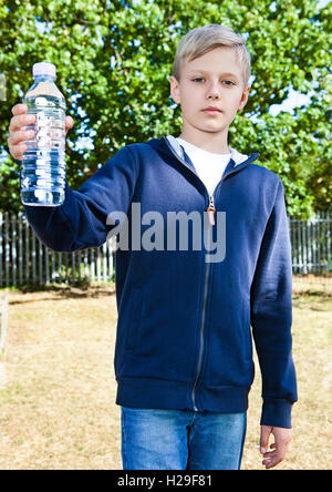 Young teenage boy with bottle of water in park - Stock Photo