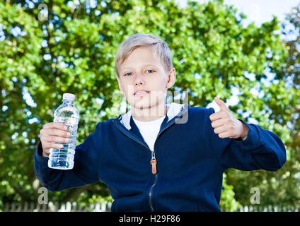 Young teenage boy with bottle of water in park sitting on the bench - Stock Photo