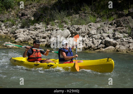 Tourism, water-sports, tourists. A smiling couple canoeing down the fast flowing turbulent waters of the Drôme River. - Stock Photo
