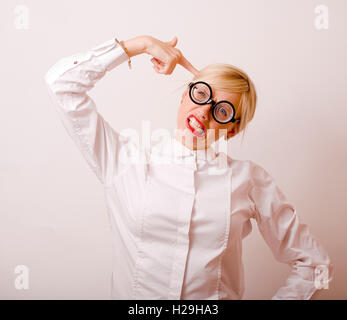 bookworm, cute young blond woman in glasses, blond hair, teenage goofy, lifestyle people concept - Stock Photo