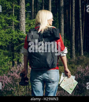Young active woman tourist standing in a clearing in the woods with a backpack, holding binoculars and a map and - Stock Photo