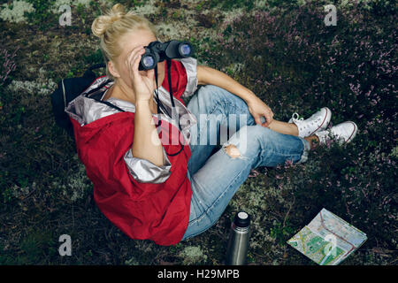 Young active woman tourist sit in a clearing in the woods with a backpack, holding binoculars and a map and looking - Stock Photo
