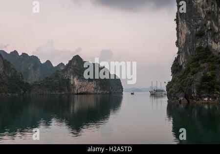 Junk boat and fishing boat between karst mountains at dawn in Halong Bay, Vietnam - Stock Photo