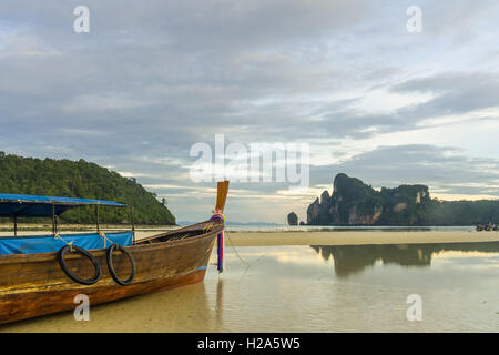 Longtail boat on Ko Phi Phi Don beach at low tide with reflection of mountains in Thailand - Stock Photo
