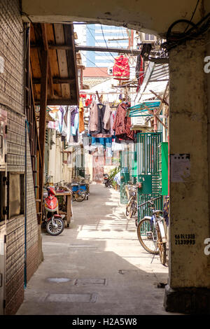 Hutong with hanging laundry and parked bicycles in Shanghai, China
