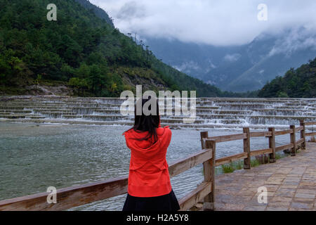 Woman tourist enjoying a view of cascading water and mist covered mountains in Yunnan, China - Stock Photo
