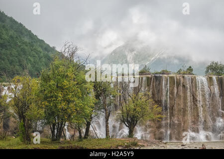 Cascading waterfall and mist covered mountains in Yunnan, China - Stock Photo