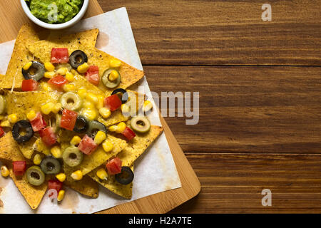 Baked nachos with cheese, green and black olives, tomato and corn, with guacamole on the side - Stock Photo