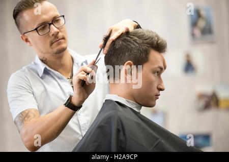 Interior shot of working process in modern barbershop. Side view portrait of attractive young man getting trendy - Stock Photo