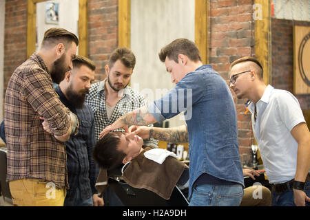 Teacher training group of students in beard shaving with metal straight razor in hairsalon. Interior shot of learning - Stock Photo