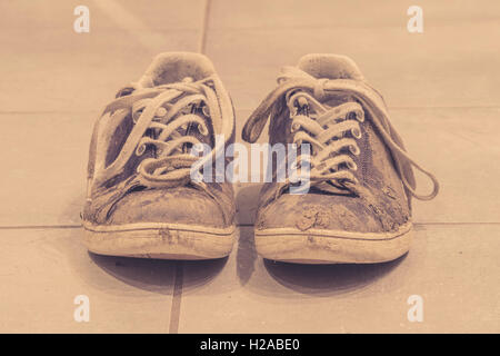Muddy sneaker shoes with laces in sepia color - Stock Photo