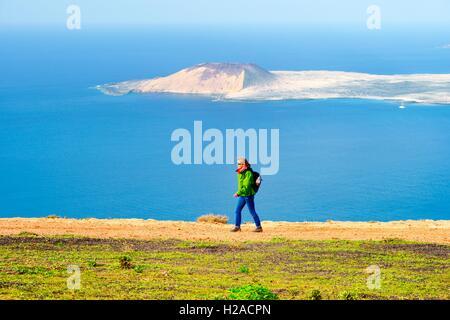 Lanzarote, Canary Islands. Woman hiking sea cliffs of Risco de Famara at Guinate 550m above Atlantic. Isla Graciosa - Stock Photo
