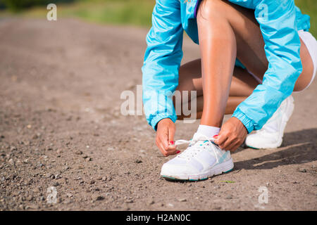 young woman tying shoelaces on sneakers - Stock Photo