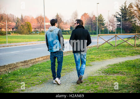Two handsome casual trendy young men, 2 friends, in an urban park walking and chatting together - Stock Photo