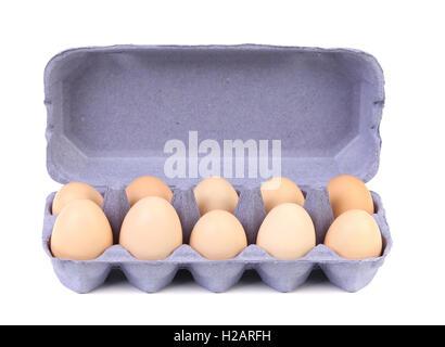 purple Cardboard egg box with ten  brown eggs - Stock Photo