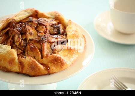 Fresh home made apple galette drizzled with salt caramel sauce on cake stand in horizontal format