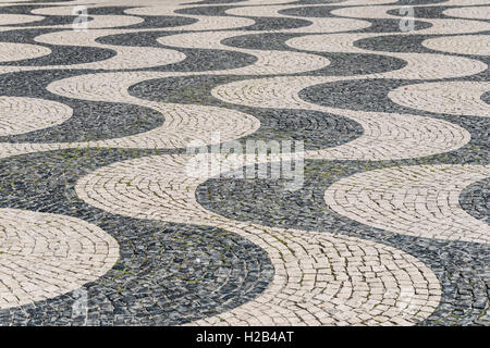 Wavy pattern in pavement, black and white, cobblestones, Rossio, Lisbon, Portugal - Stock Photo