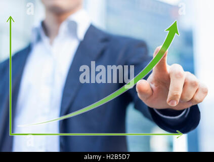 Businessman presenting a sustainable development concept with office buildings backgrounds - Stock Photo