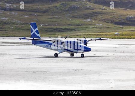 Barra, Outer Hebrides, Scotland G-SGTS - Viking DH-6-400 Twin Otter - Loganair aircraft landing at Barra Airport. - Stock Photo