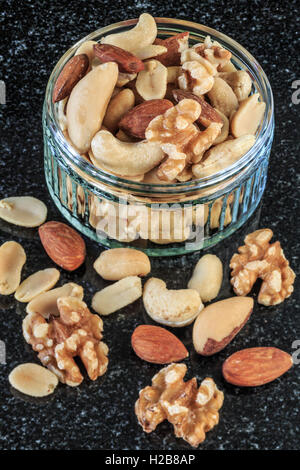 Shelled Mixed nuts in bowl Dark Background - Stock Photo