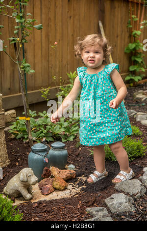 Eighteen month old girl walking outside in a garden where there are urns of ashes from pet dogs, in Issaquah, Washington, - Stock Photo