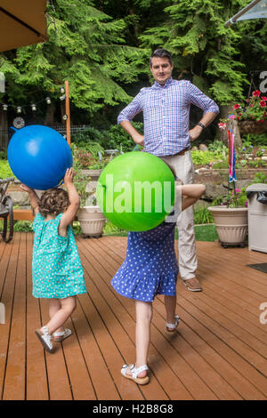 Father playfully acting brave when his three and one year old daughters are going to throw balls at him - Stock Photo
