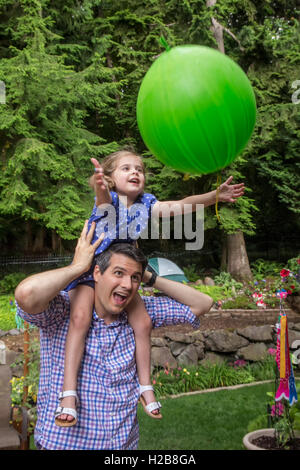 Thirty-four year old father holding his three year old daughter as she catches a balloon tossed to her - Stock Photo