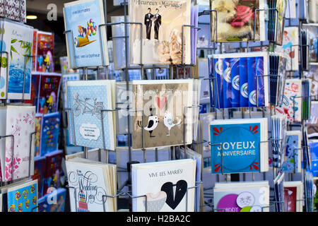 Close up view of French postcards on racks about marriages on Rue Montorgueil street in Paris. - Stock Photo