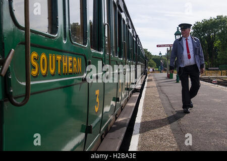 The conductor walking on the platform in Havenstreet on the Isle of Wight Steam Railway - Stock Photo