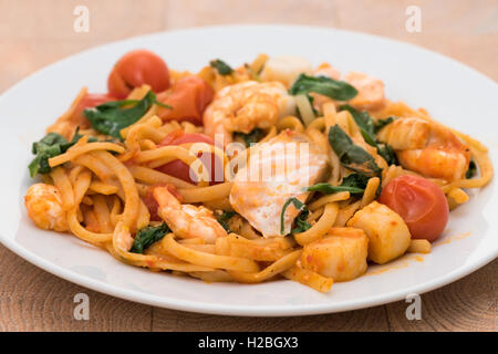 Seafood linguine pasta with king prawns, scallops, and salmon - Stock Photo