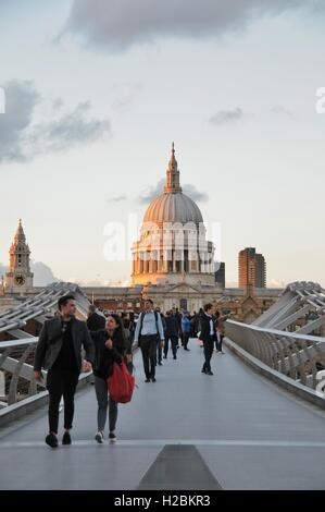 People crossing The Millennium  Bridge, with St Paul's cathedral in the background. - Stock Photo
