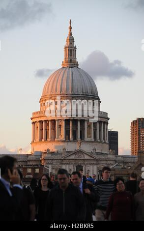 A vertical image of pedestrians crossing The Millennium Bridge, with St Paul's cathedral in the background. - Stock Photo