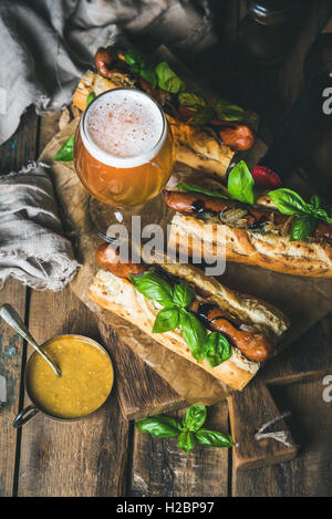 Glass and bottle of unfiltered beer, grilled sausage dogs - Stock Photo