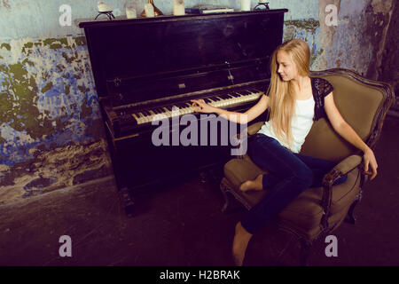 Woman Playing A Grand Piano With One Finger Stock Photo