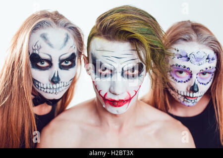 two girls and a guy with halloween face art on white background stock photo