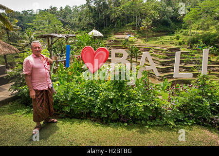 Indonesia, Bali, Tegallang, tourist wearing sarong at I love (heart) Bali sign in cafe garden - Stock Photo