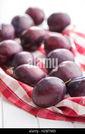 Fresh ripe plums on checkered napkin. - Stock Photo