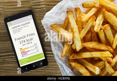 Calorie counter concept - mobile phone with calorie counter app on the screen and french fries. Wooden table as - Stock Photo