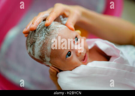 Newborn baby relaxing as mother is washing her hair - Stock Photo