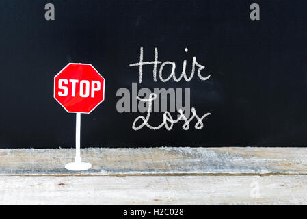 Mini STOP sign over chalkboard background and table, STOP HAIR LOSS concept - Stock Photo
