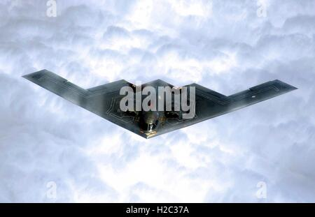 A U.S. Air Force B-2 Spirit stealth strategic bomber flies over the clouds after taking off from the Whiteman Air - Stock Photo