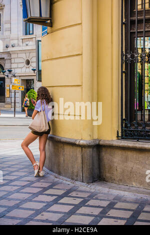 A young Spanish woman leans against a building with one leg outstretched as she talks on her cell phone in the city - Stock Photo